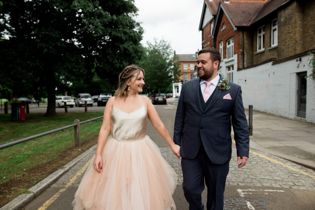 a wedding couple walking down a street in London