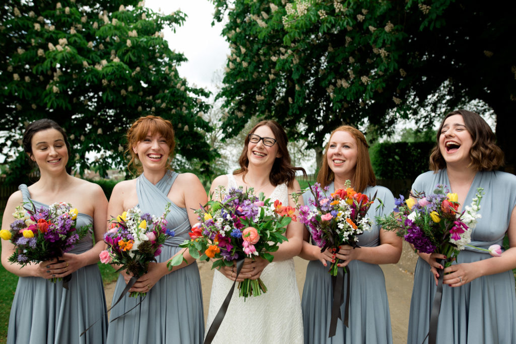 a bride lined up with her bridesmaids holding flowers