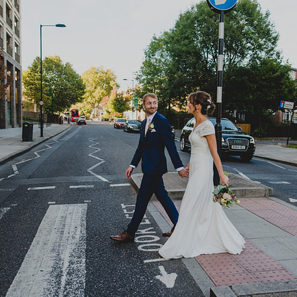 a bride and groom crossing the road in London