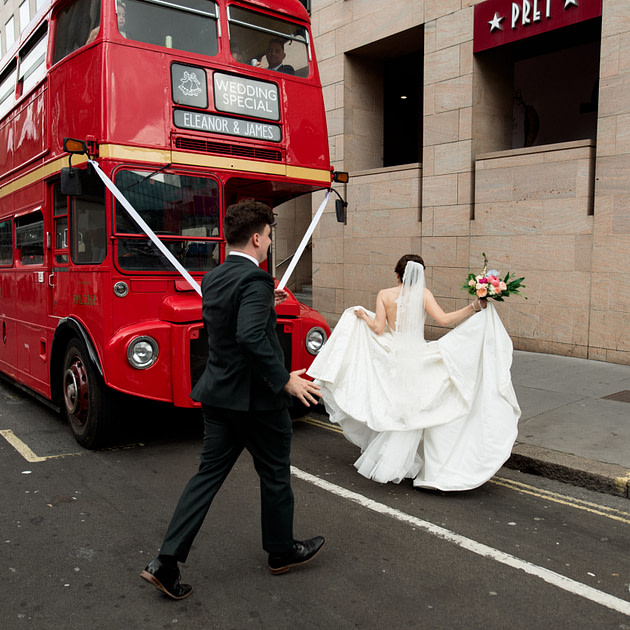 a bride and groom walking towards their red London bus