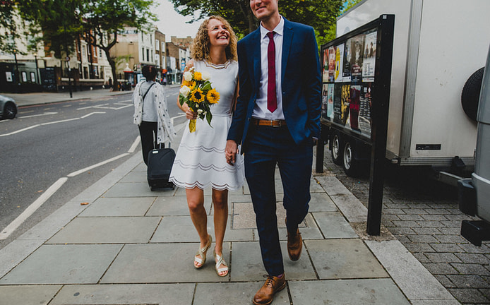 a bride and groom walking down Islington High Street